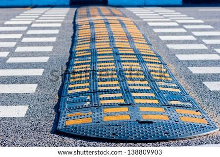 Yellow and Black Speed Bump  on asphalt. - stock photo