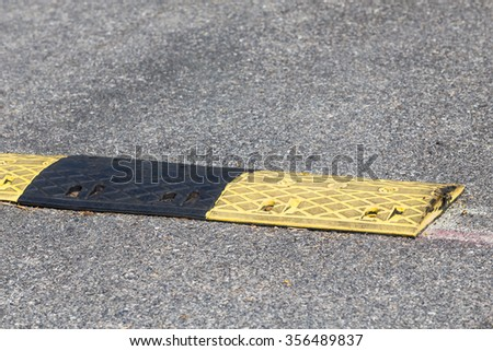 Yellow and black speed bumps on the road - stock photo