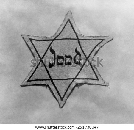 Yellow and black star which the Jews were required to wear in occupied Holland during World War 2. - stock photo