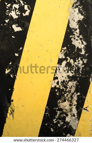 Yellow and black stripes on the concrete surface. - stock photo