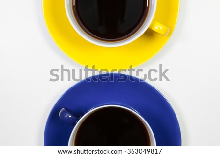 Yellow and blue cups of coffee on a white table - stock photo