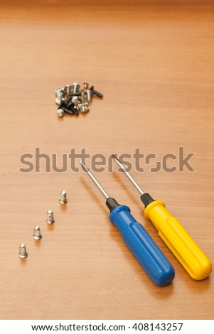 Yellow and blue screwdriver with screws on a wood background. - stock photo
