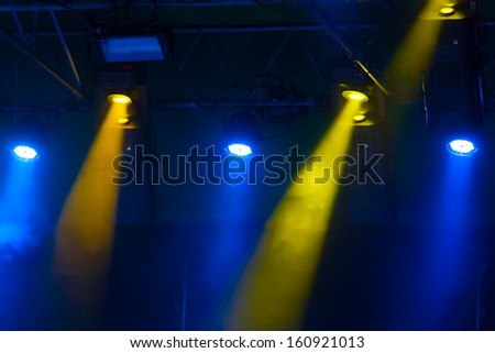 yellow and blue spotlights that illuminate the stage at a concert with fog - stock photo