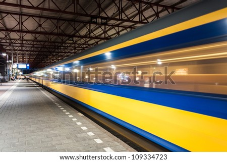 Yellow and blue train arriving in a big roofed dutch train station in the evening in the netherlands - stock photo