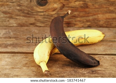 yellow and Brown banana on wooden table  - stock photo