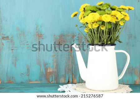 Yellow and green flowers in decorative teapot on color wooden background - stock photo