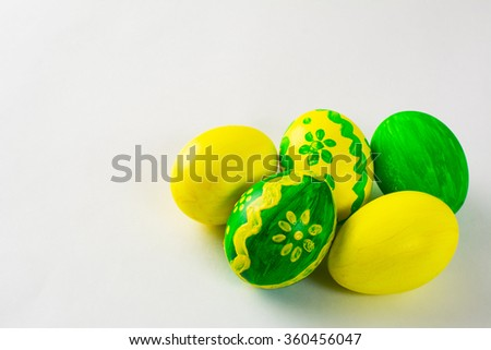 Yellow and green hand-painted Easter eggs with floral design on a white background. Easter background. Easter symbol. Copy space - stock photo