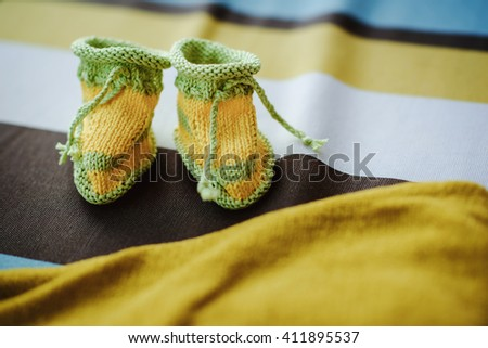 yellow and green handmade crocheted booties for a baby - stock photo