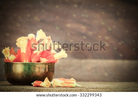 Yellow and orange flowers in grunge brass bowl with heart shaped bokeh on blurred wooden background in vintage style - stock photo