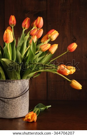 Yellow and orange tulips in old bucket on table - stock photo