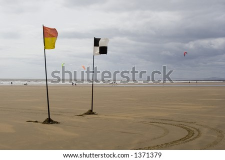 Yellow and red and chequered flags flying on beach. Life savers warning signs. Porthcawl Beach, Wales, UK. - stock photo