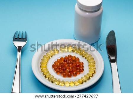 Yellow and red pills on a plate and bottle on blue background - stock photo