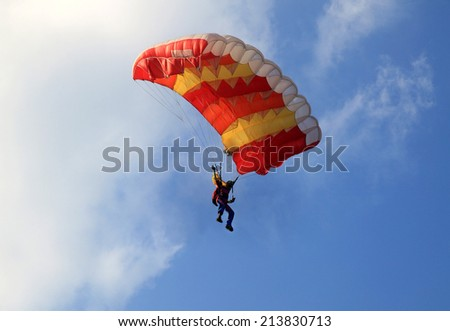 Yellow and red sail parachute on blue sky with white cloud - stock photo
