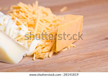 yellow and white cheddar cheese grated on a wood cutting board - stock photo