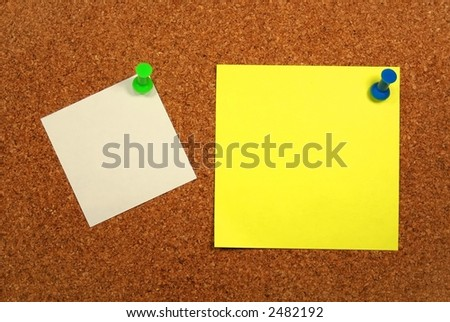 Yellow and white papers attached to a corkboard. - stock photo