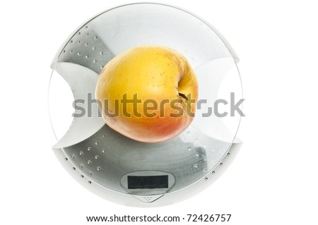 Yellow apple isolated on food scale - stock photo