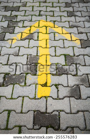 Yellow arrow on gray cobblestone pavement, road direction sign - stock photo