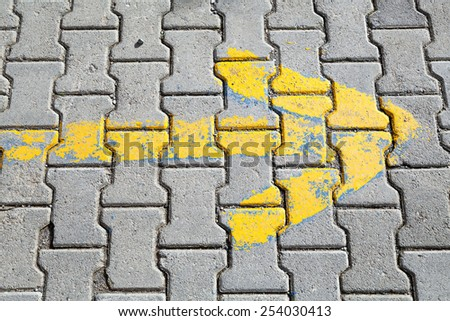 Yellow arrow painted on gray cobblestone pavement, road direction sign shows right way - stock photo