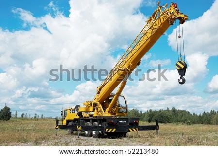 yellow automobile crane with risen telescopic boom outdoors over blue sky - stock photo