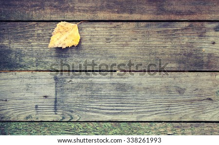 Yellow autumn leaf lays on a dark gray wooden table made of boards, background texture with retro style tonal correction photo filter effect - stock photo