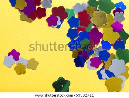 yellow background with confetti in the shape of flowers - stock photo