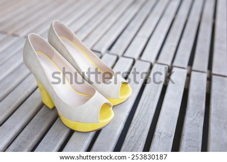 yellow ballet shoes and high heels open toe shoes on wood boards - stock photo