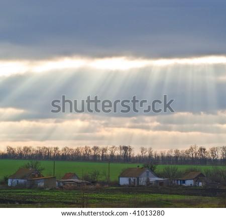 Yellow beams of the sun falling on evening village - stock photo