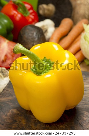 """yellow bell pepper on cutting board in front of assortment of fresh salad ingredients""""yellow bell pepper"""" - stock photo"""