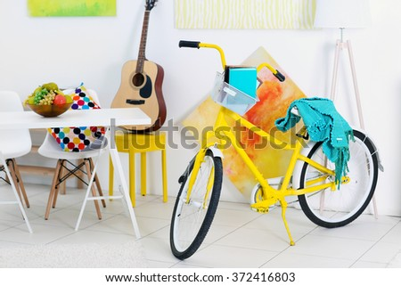 Yellow bicycle with blue cover in light living room interior - stock photo
