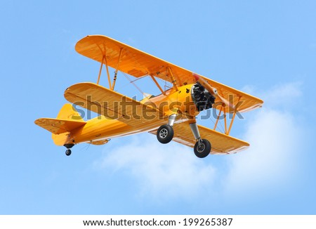 Yellow biplane on the blue sky. - stock photo