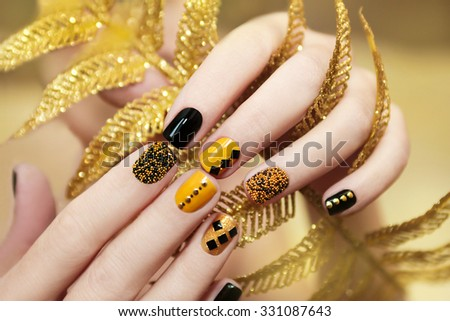 Yellow black manicure with metallic crystals of different shapes and colors on short nails. - stock photo
