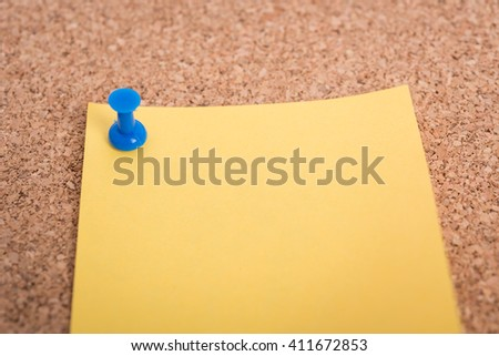 Yellow blank note papers with pin on wooden board background - stock photo