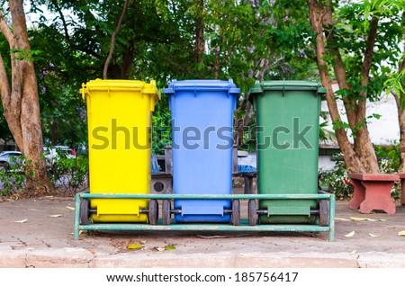 Yellow, blue, green bins , Recycling bins , Public trash , Trash under the tree - stock photo