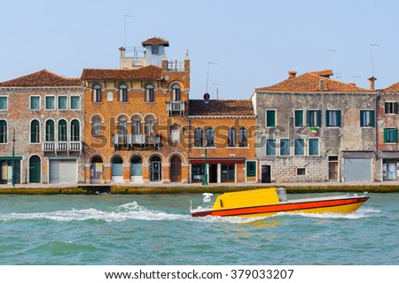 Yellow boat in Grand Canal, Venice, Italy. Bright sunny panorama view of Grand Canal with old brick buildings. Beautiful photo background of the venetian canal. - stock photo