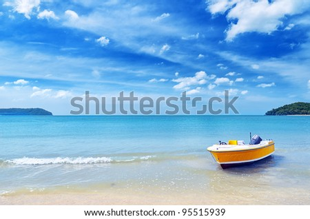 Yellow boat on a beach. - stock photo