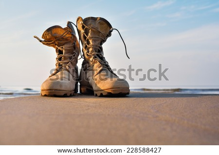 Yellow boots with a shoelaces on a sandy beach - stock photo