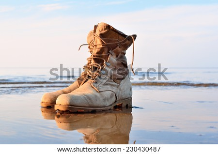 Yellow boots with a shoelaces on a wet sandy beach - stock photo
