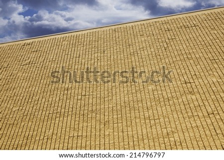 yellow brick wall with clouds - stock photo