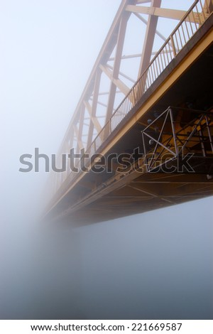 Yellow bridge disappears in the thick autumn fog.  - stock photo
