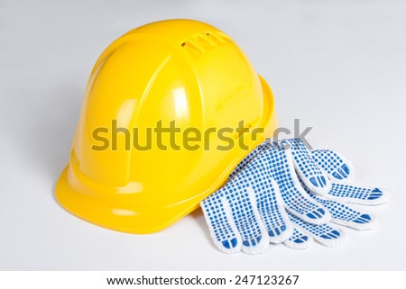 yellow builder's helmet and work gloves over white background - stock photo