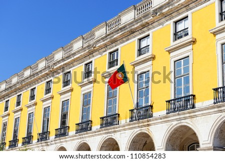 yellow building with portuguese flag surrounding Commerce Square in Lisbon, Portugal - stock photo