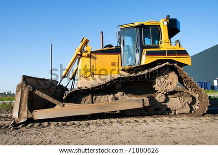 Yellow bulldozer on a clear blue day - stock photo