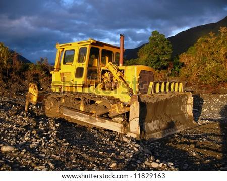 Yellow bulldozer on a sunny day - stock photo