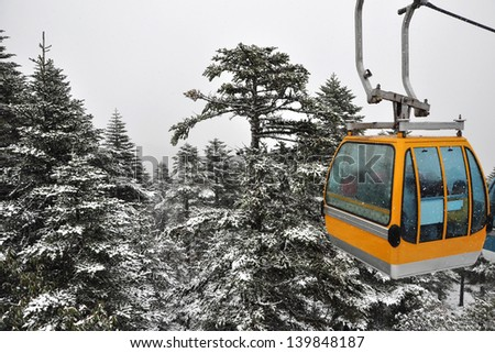 Yellow cable car in snow - stock photo