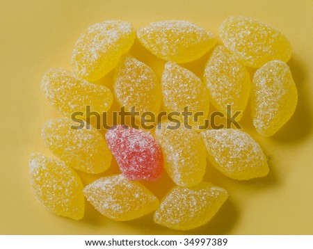 yellow candies with one red on yellow background - stock photo