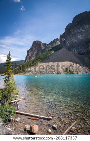 Yellow Canoe in the beautiful Lake Louise near Banff Alberta among the towering rocky mountains and teal blue crystal clear water - stock photo