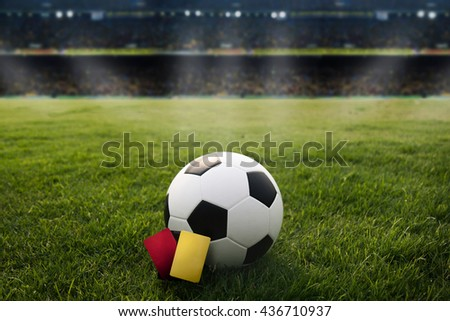 Yellow card and Red card. soccer field and soccer stadium with fans the night light before the match. - stock photo