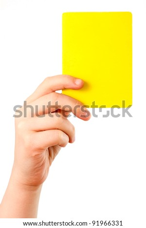 Yellow card in a hand in front of a white background - stock photo