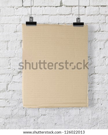 yellow cardboard poster on brick wall - stock photo