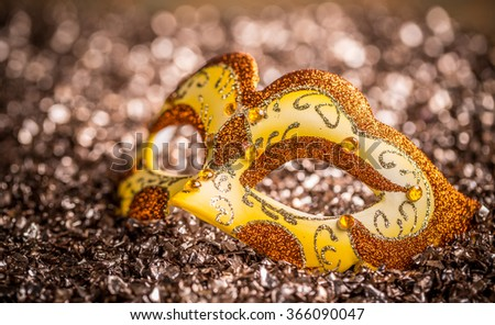 Yellow carnival mask on glittering background - stock photo